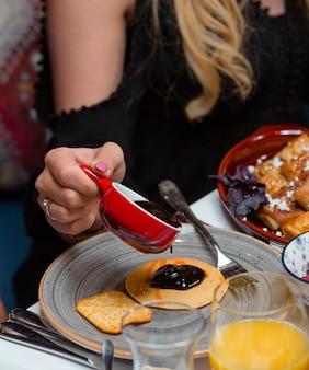 Vrouw giet jam op pannenkoek voor het ontbijt