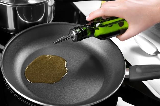 Vrouw giet olie uit fles in koekenpan in keuken