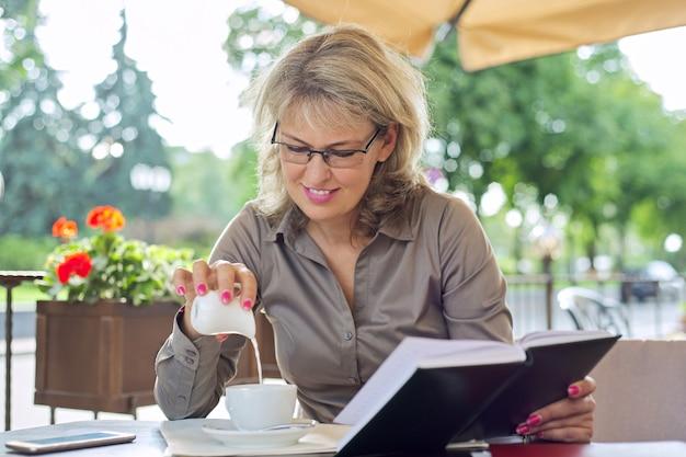 Vrouw gieten melk in een kopje met koffie op een terras