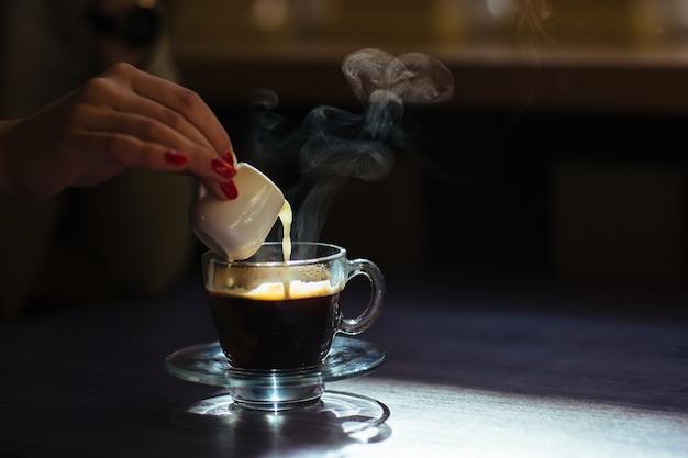 Vrouw gieten melk in haar koffie
