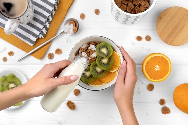 Vrouw gieten melk in volkoren vlokken met sinaasappel en kiwi's