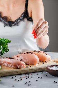 Vrouw gieten peper op kippenborsten op snijplank met zout op grijze ondergrond