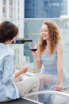 Vrouw gieten rode wijn in glas van haar mooie lachende vriendin wanneer ze 's avonds op het dak doorbrengen