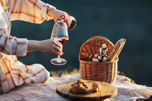 Vrouw gieten rode wijn tijdens het rusten op picknick