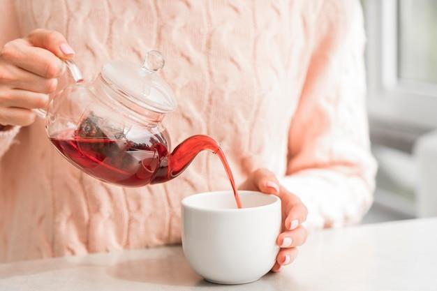 Vrouw gieten thee in de beker
