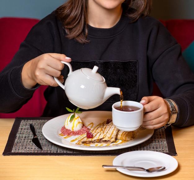Vrouw gieten thee met dessert in restaurant