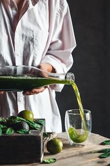 Vrouw gieten vers gemengde groene en witte smoothie in glazen pot met ingrediënten rond op een rustieke houten tafel