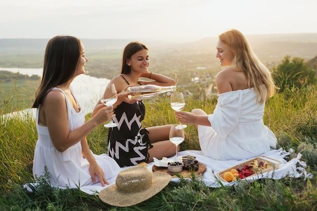 Vrouw gieten wijn zittend op picknick buitenshuis. concept van picknicken tijdens zomervakantie of weekends.
