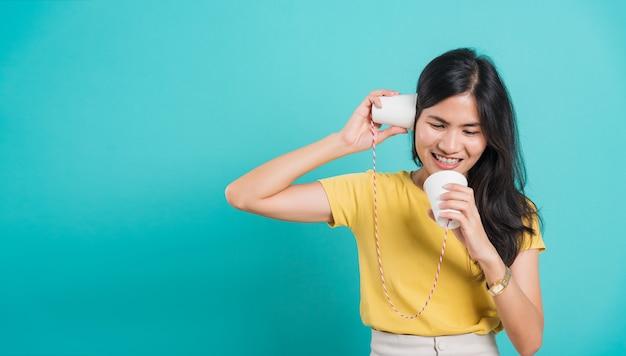 Vrouw glimlach witte tanden permanent dragen gele t-shirt, ze papier houden kan telefoneren