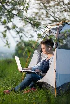 Vrouw glimlachen die in openlucht aan haar laptop in een tent werken terwijl het kamperen aard