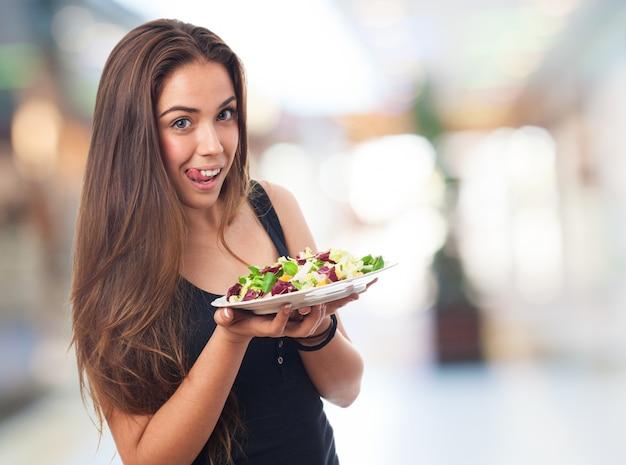 Vrouw glimlachend met een salade in handen
