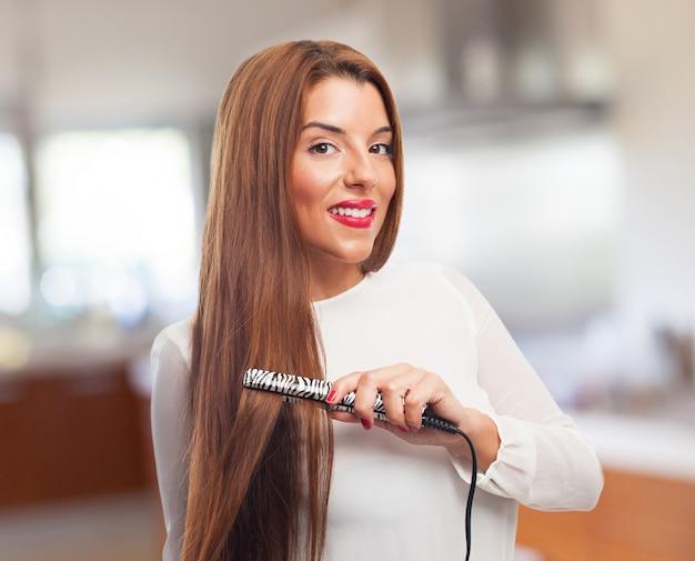 Vrouw glimlachend, terwijl het effenen van haar haren