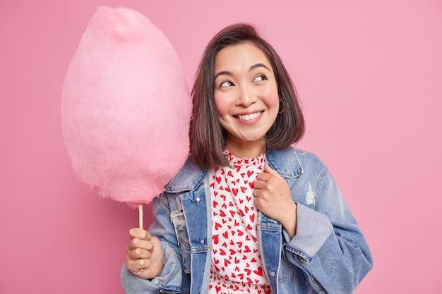 Vrouw glimlacht aangenaam kijkt weg heeft dromerige uitdrukking gekleed in spijkerjasje houdt smakelijk zoet suikerspin draagt stijlvol spijkerjasje