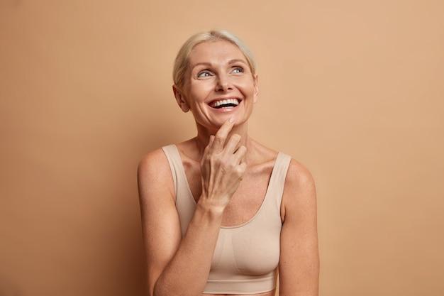 Vrouw glimlacht breed geconcentreerd hierboven heeft een perfect verzorgde huid denkt aan iets aangenaams draagt een casual top geïsoleerd op bruin