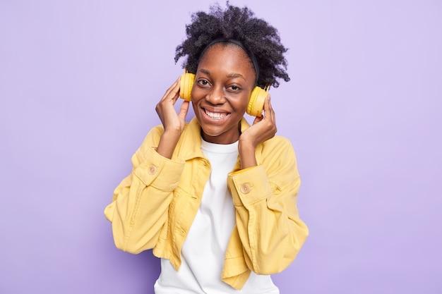 Vrouw glimlacht breed houdt handen op draadloze koptelefoon brengt vrije tijd door met favoriete muziek draagt gele jas geïsoleerd op paars