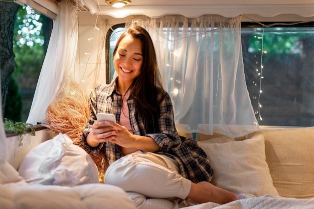 Vrouw glimlacht en kijkt op haar mobiele telefoon
