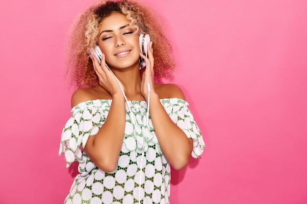 Vrouw glimlacht en luistert naar muziek in een koptelefoon