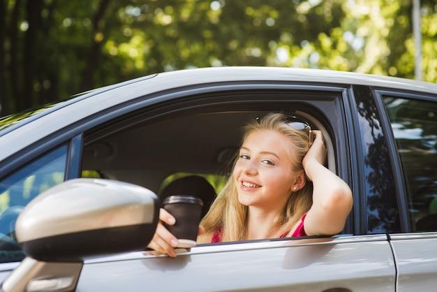 Vrouw glimlacht en poseert in de auto bestuurdersstoel