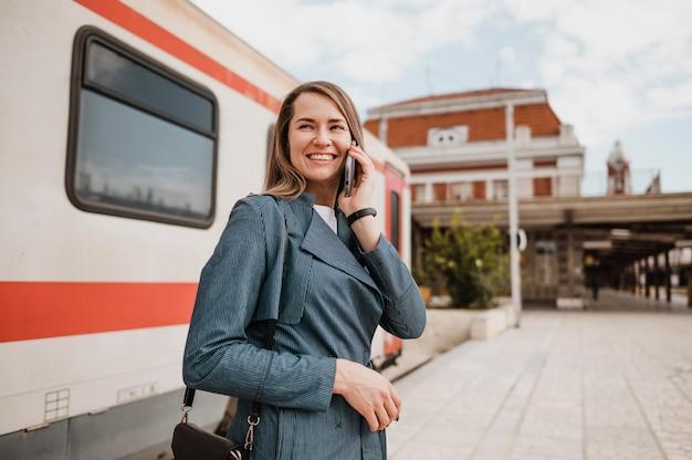 Vrouw glimlacht en praat op mobiele telefoon op het treinstation