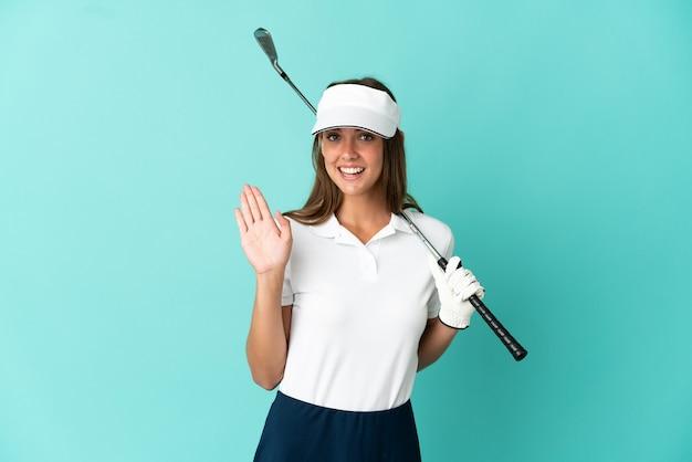 Vrouw golfen over geïsoleerde blauwe achtergrond die met de hand salueert met een gelukkige uitdrukking