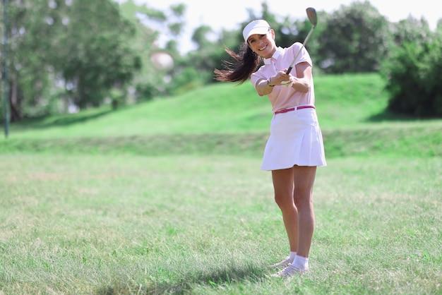 Vrouw golfer met golfclub in de hand en vliegende bal na het raken