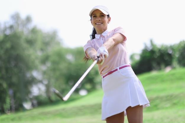 Vrouw golfer met putter in de hand na het raken.