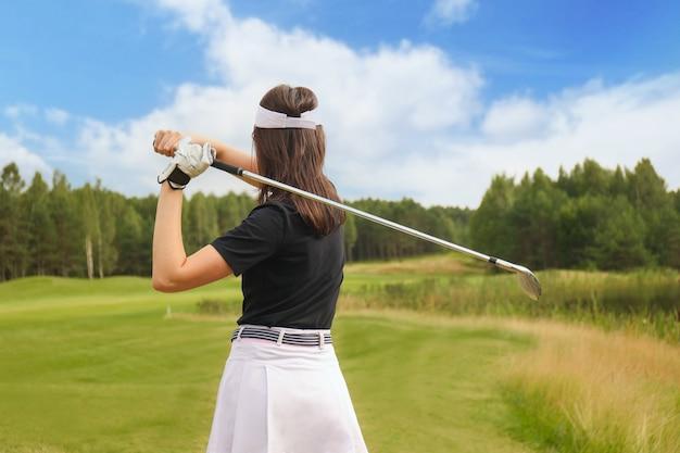 Vrouw golfer slaat een fairway schot richting het clubhuis.