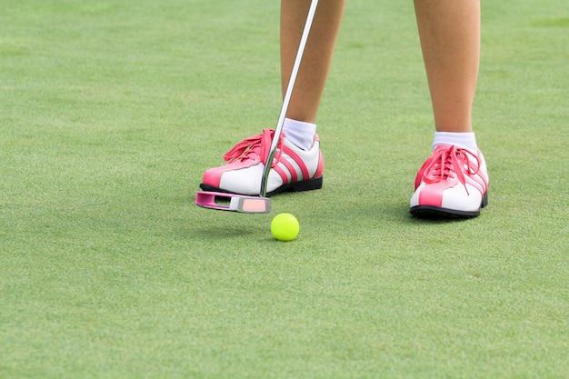 Vrouw golfspeler zetten op de green