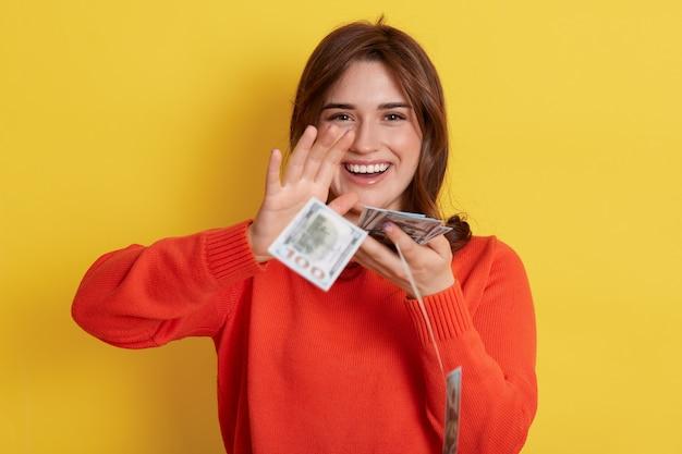 Vrouw gooit contant geld, loterijwinnaar met zeer gelukkige uitdrukking, glimlachend, dame met bankbiljetten binnen, donkerharig meisje met haar munt, heeft beloning.