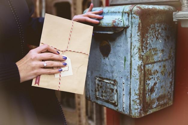 Vrouw gooit een envelop van de kerstman in een oude vintage brievenbus