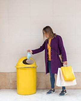 Vrouw gooit een gezichtsmasker in een gele vuilnisbak terwijl ze boodschappentassen vasthoudt