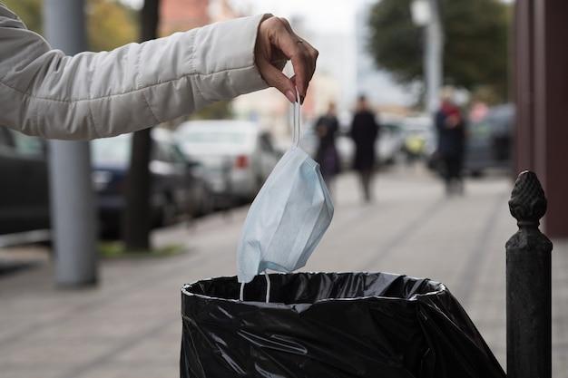 Vrouw gooit een gezichtsmasker naar een openbare vuilnisbak in een stadsstraat