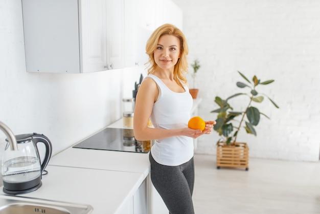 Vrouw gooit een oranje, fit ontbijt