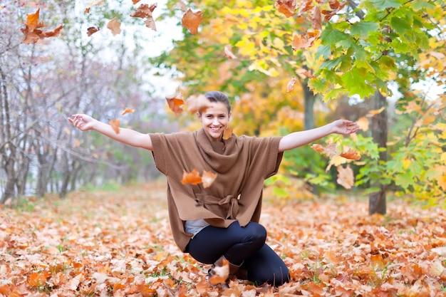 Vrouw gooit herfstbladeren