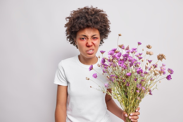 Vrouw grijnst gezicht heeft verstopte neus roodheid rond ogen reageert op trekker houdt boeket van wilde bloemen heeft last van hooikoortssymptomen geïsoleerd over wit