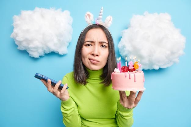 Vrouw grijnst gezicht kijkt ongelukkig naar camera heeft slecht humeur op haar verjaardag poses met heerlijke taart en smartphone geïsoleerd op blauw