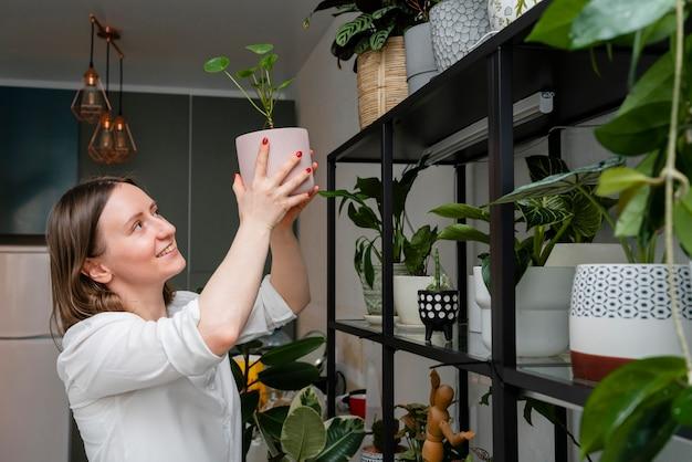 Vrouw groeiende planten thuis