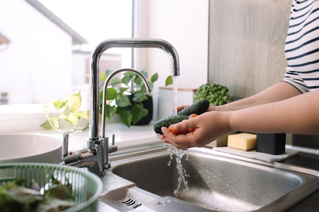 Vrouw groene komkommers wassen voor salade in de keuken in de gootsteen onder stromend water.