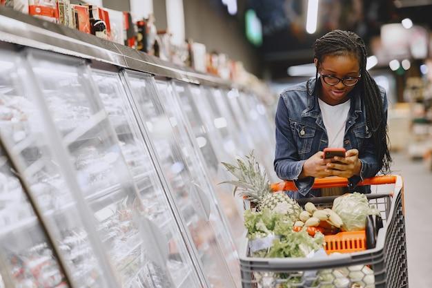 Vrouw groenten winkelen bij de supermarkt