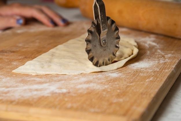 Vrouw gutab maken op een houten bord. nationale keuken van azerbeidzjan.
