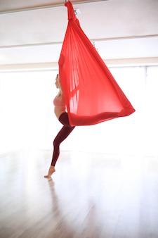 Vrouw gymnastiek- yoga opleiding met rood linnen