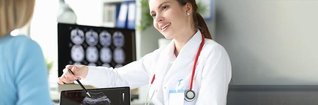 Vrouw gynaecoloog die foetale echografie op digitale tablet toont aan patiënt