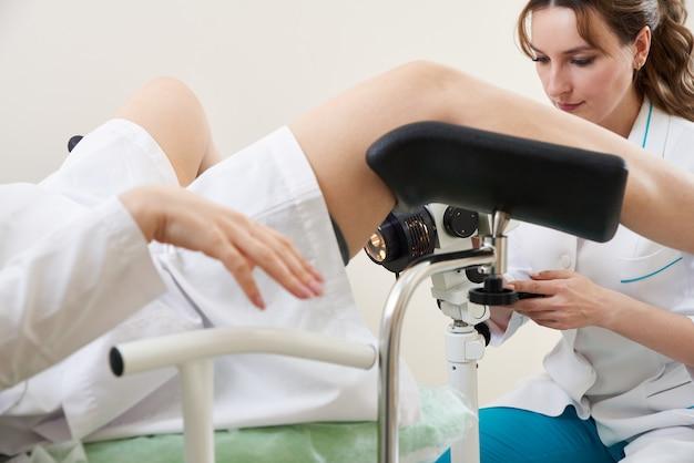 Vrouw gynaecoloog werken met colposcoop en maakt microscopisch onderzoek in kliniek