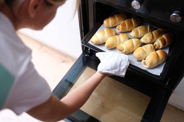 Vrouw haalt bakplaat met gekookte croissants uit de ovenclose-up