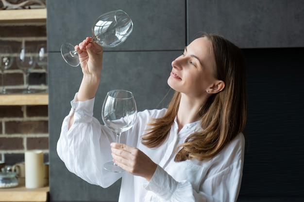 Vrouw haalt een glas uit de vaatwasser terwijl ze in de keuken staat