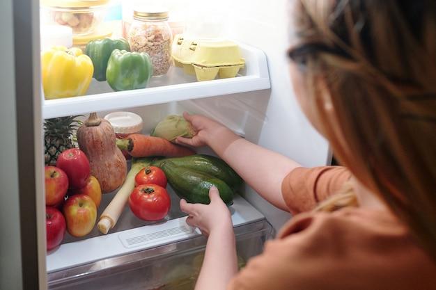 Vrouw haalt verse courgette uit de koelkast om een gezond, heerlijk gerecht te maken voor het avondeten