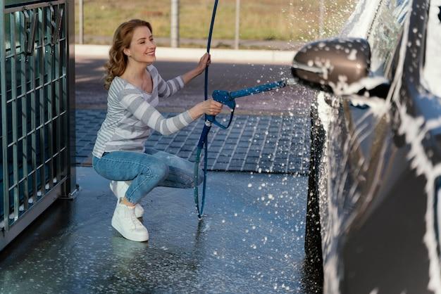 Vrouw haar auto buiten wassen