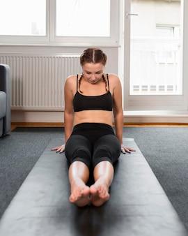 Vrouw haar benen binnenshuis strekken
