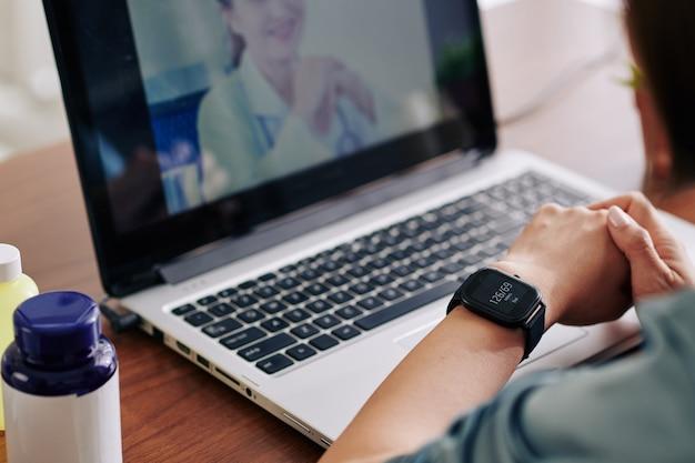 Vrouw haar bloeddruk controleren via applicatie op smartwatch en vertellen aan virtuele arts