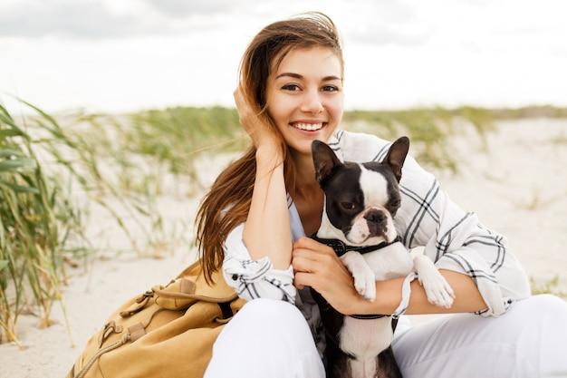 Vrouw haar bulldog knuffelen op het strand bij zonsondergang licht, zomervakantie. stijlvol meisje met grappige hond rusten, knuffelen en plezier maken, leuke momenten.